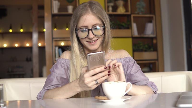 背景中断咖啡新月形面包杯子甜点 妇女给朋友和微笑写消息 免版税库存图片