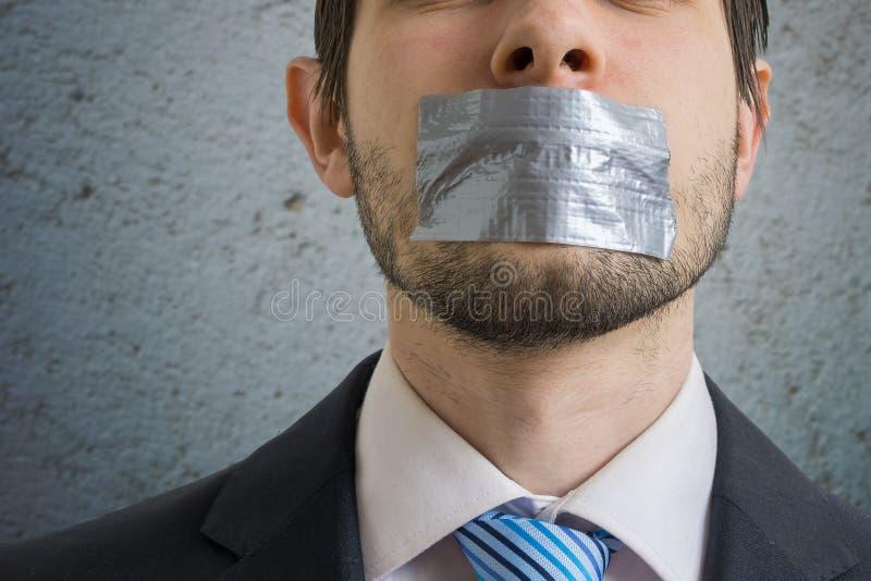 背景企业审查概念查出人二白色 人沉默与在他的嘴的橡皮膏 免版税库存照片