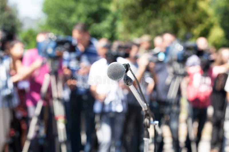 背景会议查出话筒新闻白色 话筒在焦点,被弄脏的照相机操作员 库存照片