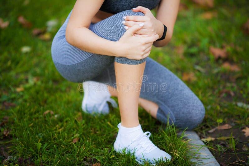 背景伤害查出的行程白色 在膝盖的美好的妇女感觉痛苦 免版税图库摄影