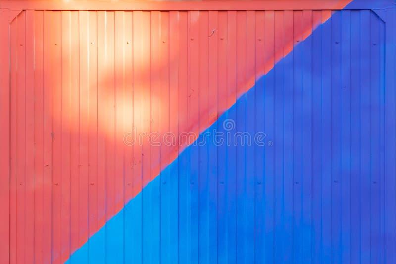 背景做了在蓝色和红色绘的金属外形在后照的篱芭或容器 库存图片