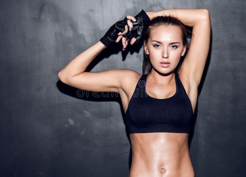 背景健身灰色墙壁妇女年轻人 免版税库存图片