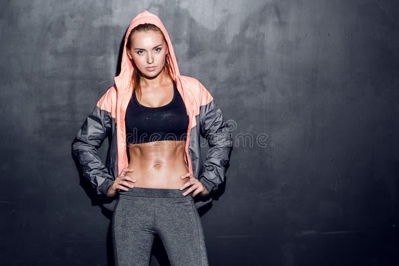 背景健身灰色墙壁妇女年轻人 免版税图库摄影