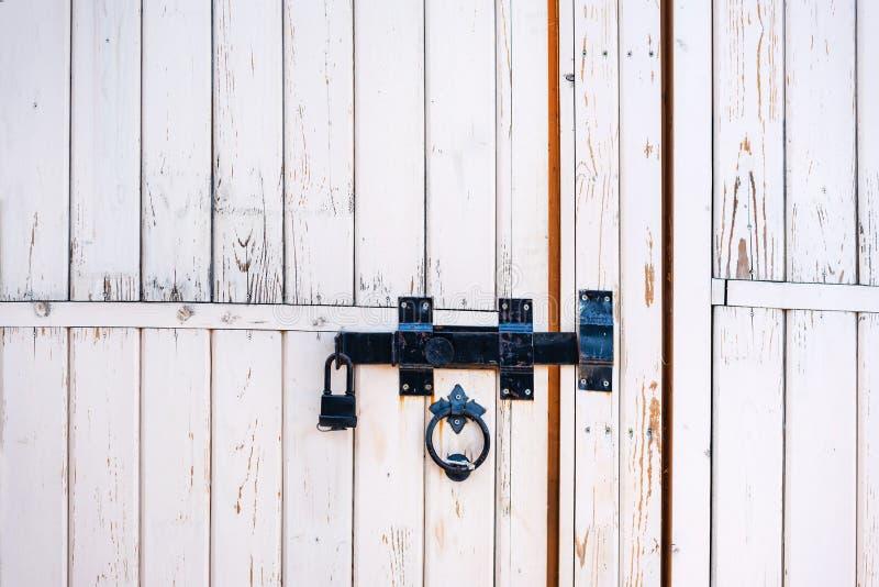 背景和纹理:老白色木门,关闭与传统伪造的金属锁 库存照片