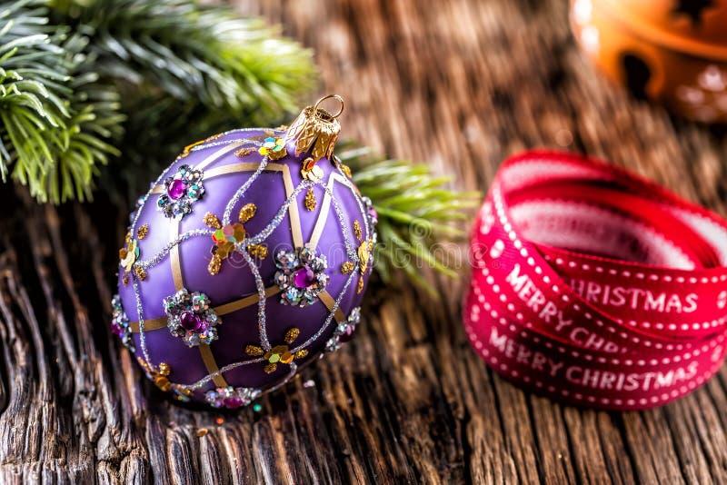 背景圣诞节关闭红色时间 豪华金黄紫色蓝色圣诞节球和装饰 与文本愉快的圣诞节的红色丝带 免版税库存图片