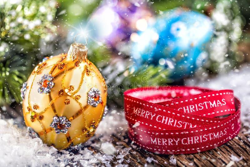 背景圣诞节关闭红色时间 豪华金黄紫色蓝色圣诞节球和装饰 与文本愉快的圣诞节的红色丝带 免版税库存照片