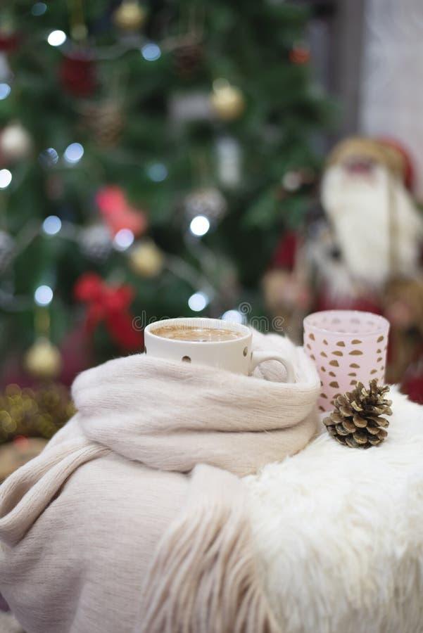 背景圣诞节关闭红色时间 巧克力热饮、一个杯子在一把毛皮椅子的热奶咖啡在与球的一棵大圣诞树前面和光 温暖 库存图片