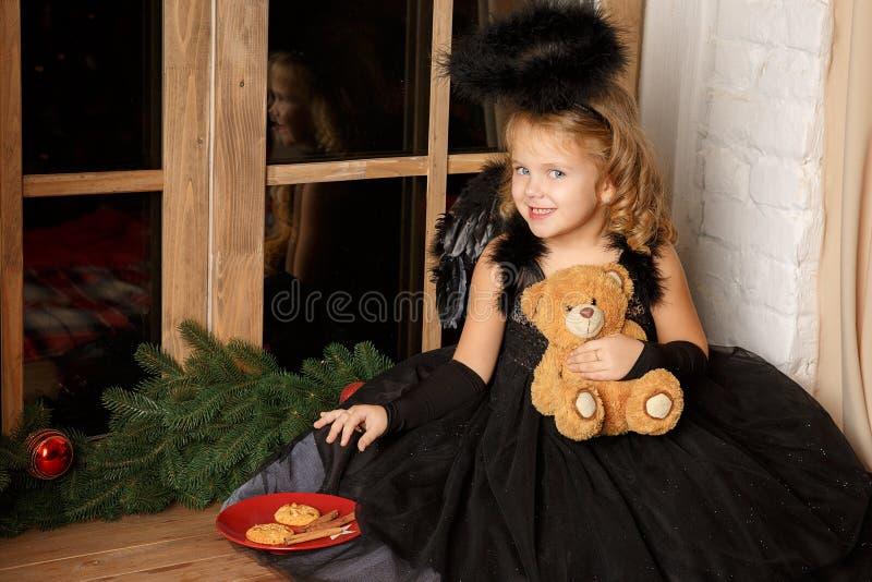 背景圣诞节构成的节假日场面 一个小白肤金发的女孩的画象,一套黑天使服装的窃取圣诞老人` s曲奇饼在窗口附近 库存图片