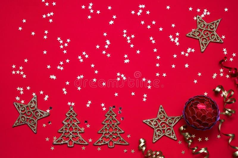 背景圣诞节红色 圣诞节装饰品和金黄星在明亮的红色背景 顶视图,拷贝空间 免版税图库摄影