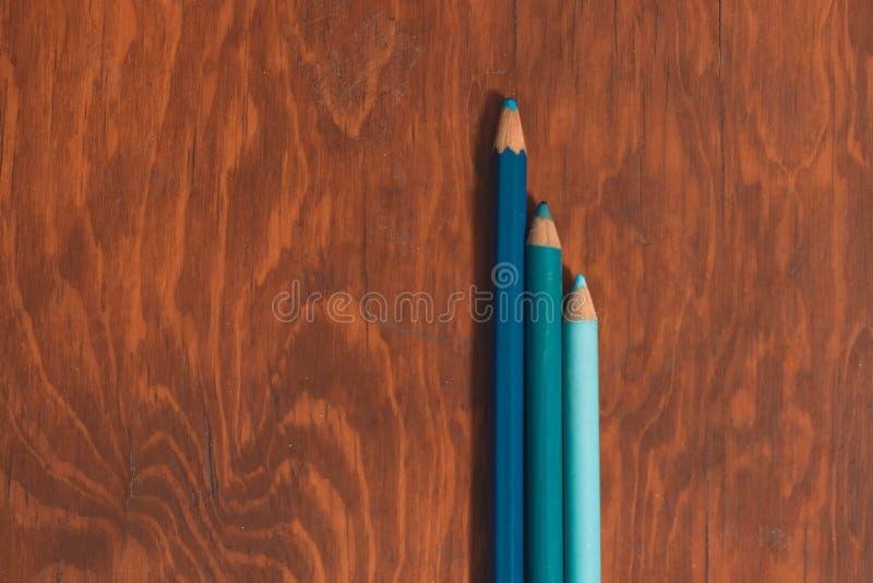 背景孤立的木质书桌上的三支彩色铅笔,以填充复印空间 库存照片