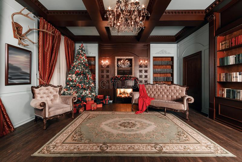 背景对光检查圣诞节构成黑暗的夜间新的s玩具年 与一盏白色壁炉、装饰的树、沙发、大窗口和枝形吊灯的经典公寓 库存图片
