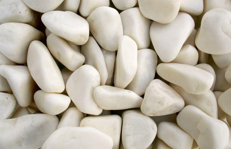 背景小卵石向白色扔石头 库存图片