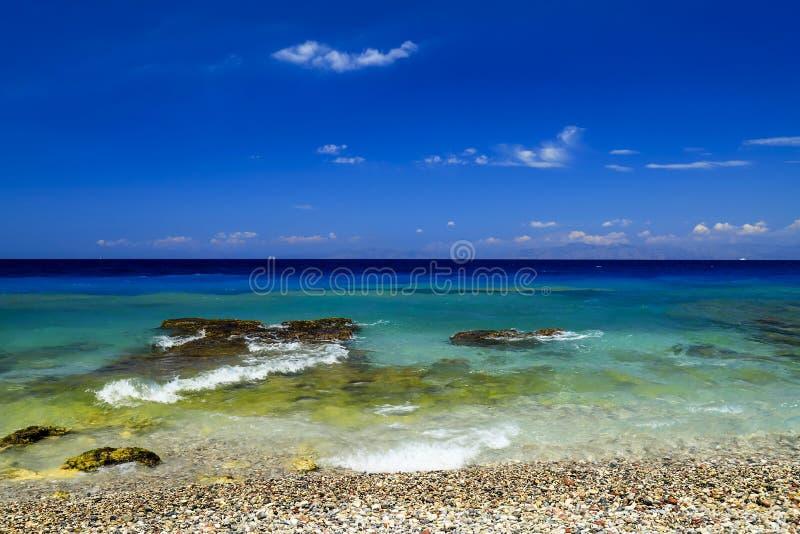 背景峡湾光芒海运星期日 美丽如画的夏天海滩,在美丽的绿松石海,罗得岛,Greee的小卵石 库存图片
