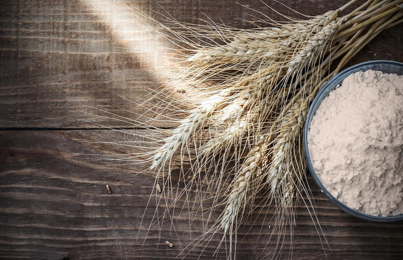 背景干麦子耳朵和面粉在老木桌上 图库摄影