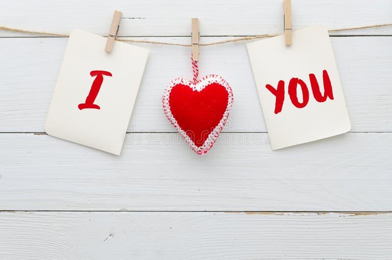 背景我爱你 `我爱你` 心脏和笔记与词'我爱你' 在白色木背景 平的被放置的conceps 免版税图库摄影