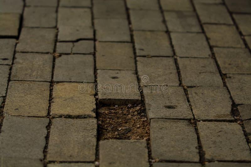 背景或纹理从一个残破和相等的瓦片有光和下落补丁的  在边路的石块 免版税图库摄影