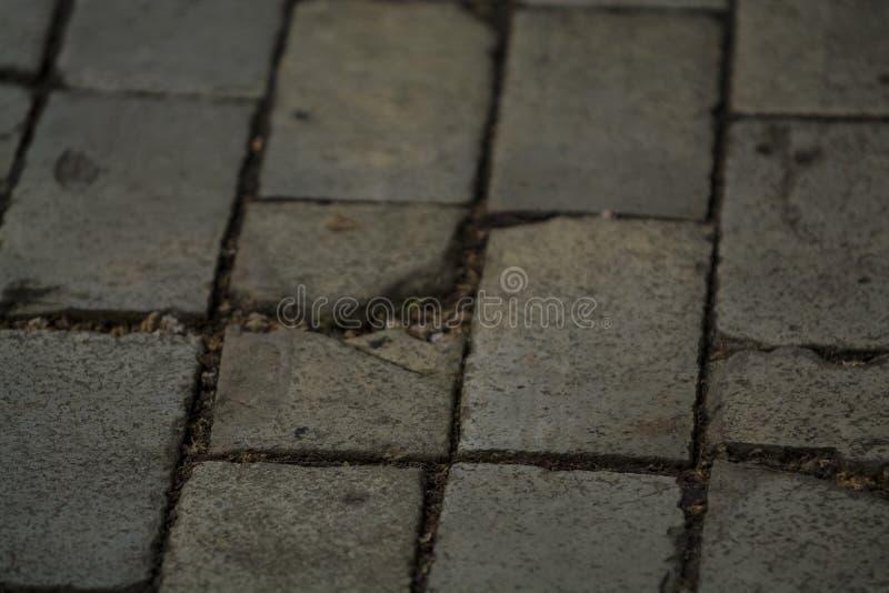 背景或纹理从一个残破和相等的瓦片有光和下落补丁的  在边路的石块 免版税库存图片