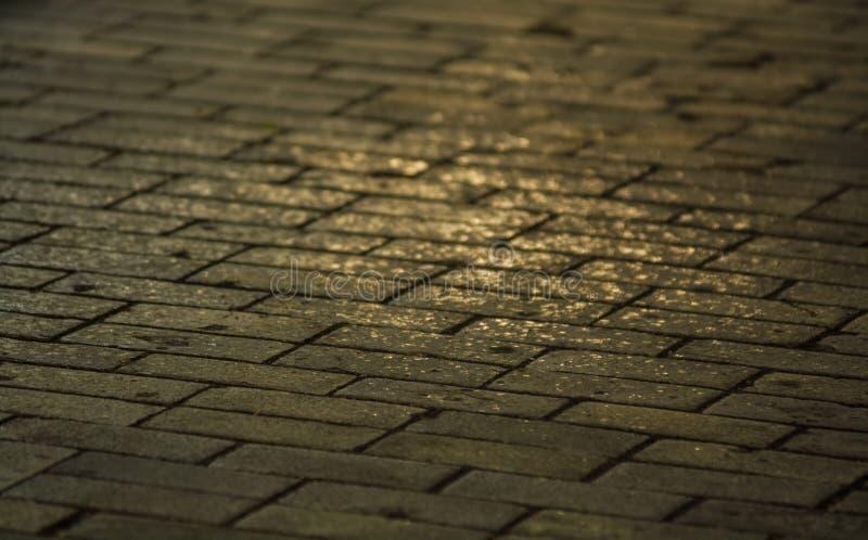 背景或纹理从一个残破和相等的瓦片有光和下落补丁的  在边路的石块 库存图片