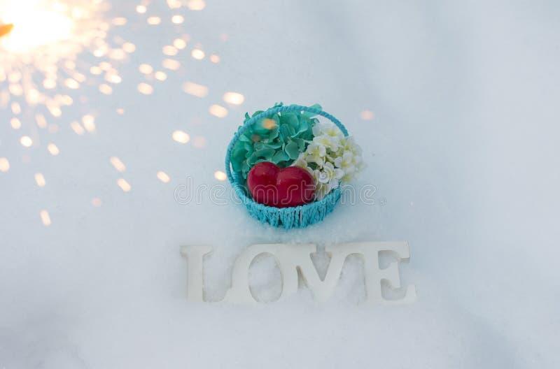 背景日国际红色印花税白人妇女 3月8日和情人节 与花的篮子在白雪背景 图库摄影