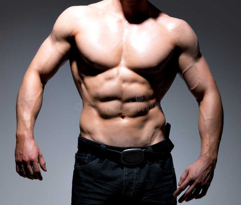 背景机体牛仔裤供以人员肌肉红色射击工作室年轻人 库存照片