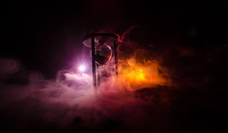 背景概念查出的目的程序时间白色 滴漏时钟和老葡萄酒木时钟剪影有箭头的和烟在黑暗的背景与热的黄色ora 免版税库存照片