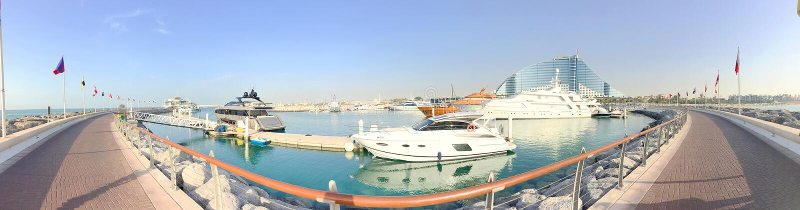背景波斯湾的全景视图,小游艇船坞和Jumeirah旅馆、游艇和水的走的区域停放 库存图片