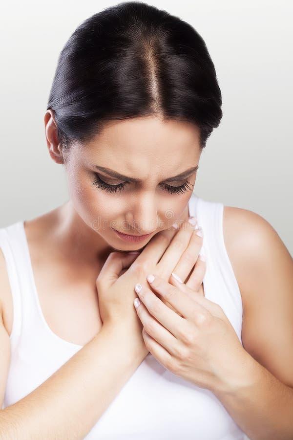 背景现有量查出在安排病的喉咙痛白人妇女 女孩握她的在喉头的胳膊 冷 英国人的 痛苦的情况 健康的概念 在一个灰色背景 库存照片