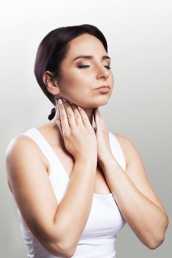 背景现有量查出在安排病的喉咙痛白人妇女 女孩握她的在喉头的胳膊 冷 英国人的 痛苦的情况 健康的概念 在一个灰色背景 库存图片