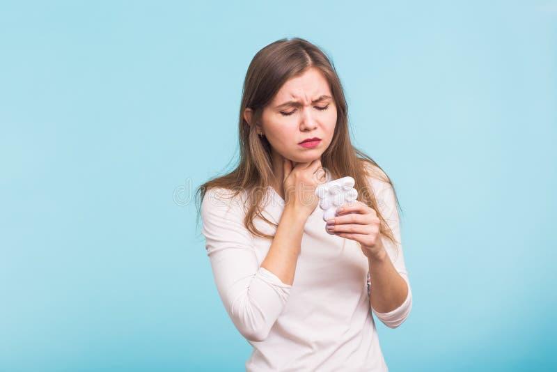背景现有量查出在安排病的喉咙痛白人妇女 接触在蓝色背景的妇女脖子 库存照片