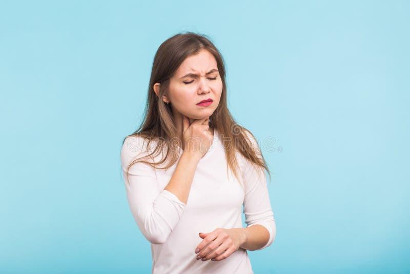 背景现有量查出在安排病的喉咙痛白人妇女 接触在蓝色背景的妇女脖子 库存图片