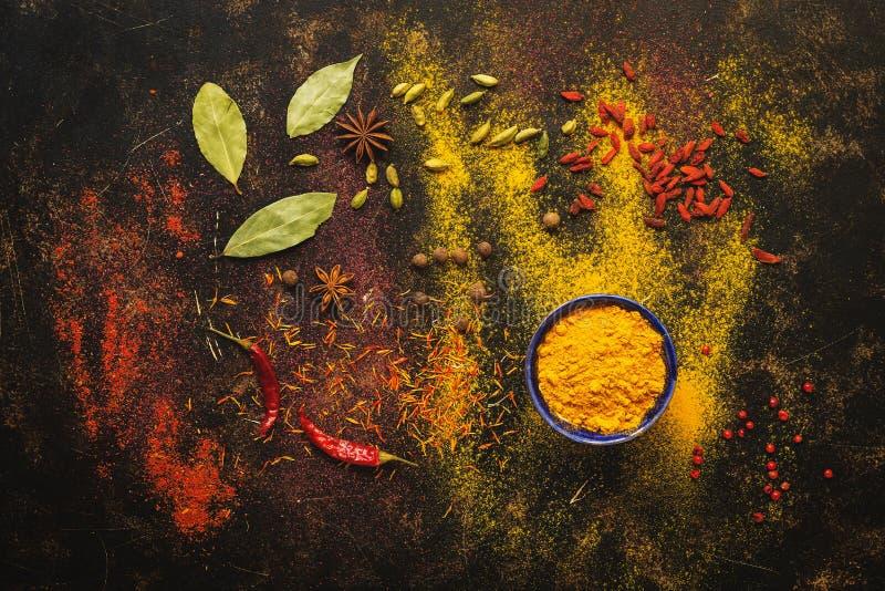 背景用用多彩多姿的香料 印度和中国香料 豆蔻果实,姜黄,goji莓果,姜黄,番红花,辣椒 免版税图库摄影