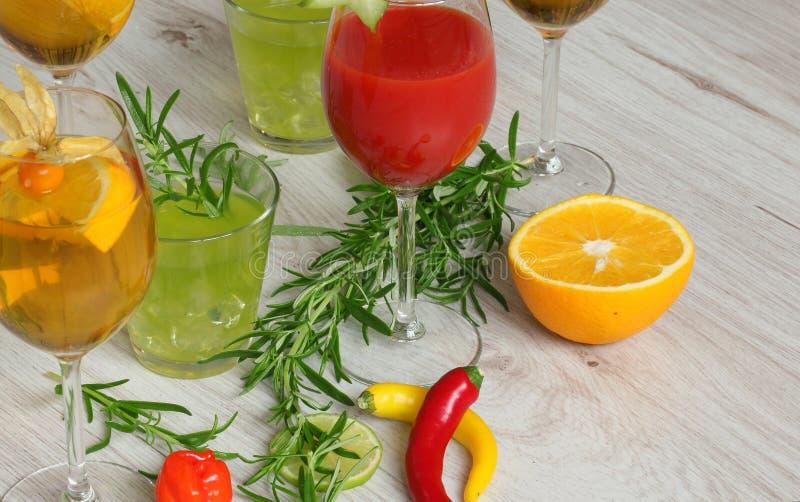 背景用饮料-五颜六色coctails、桔子,辣椒和rosemay一起 免版税库存照片