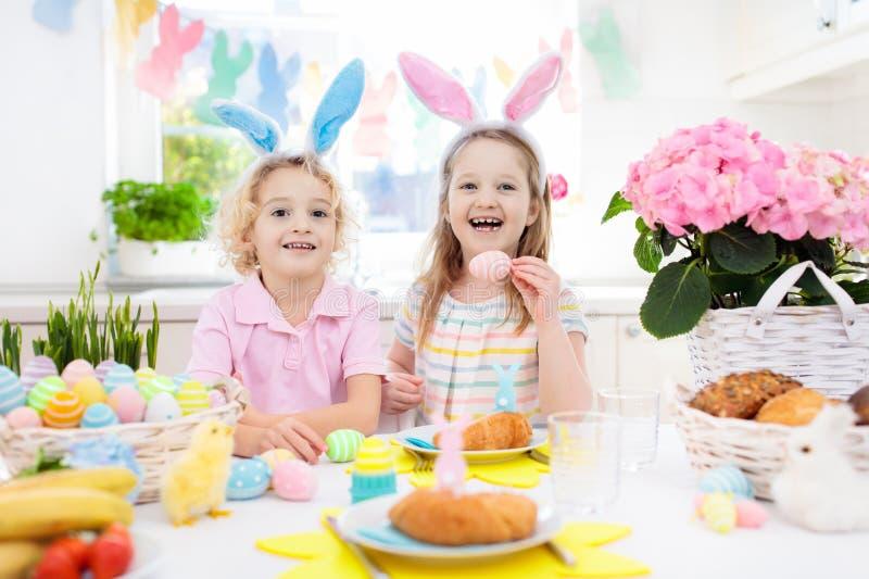 背景男孩逗人喜爱的复活节彩蛋蛋新草绿色隐藏的搜索查出搜索白色 与兔宝宝耳朵和篮子的孩子 免版税库存照片