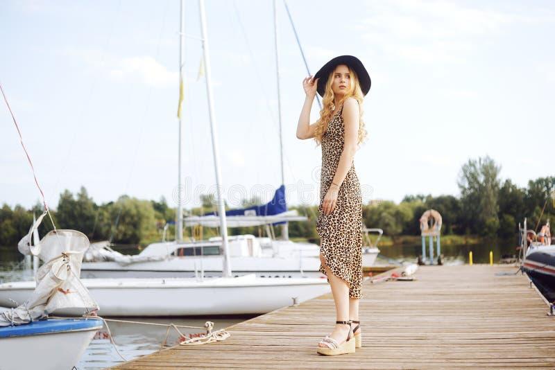 背景的女孩游艇,帆船微笑,看照相机 美丽的金发碧眼的女人坐码头,在礼服 免版税库存图片