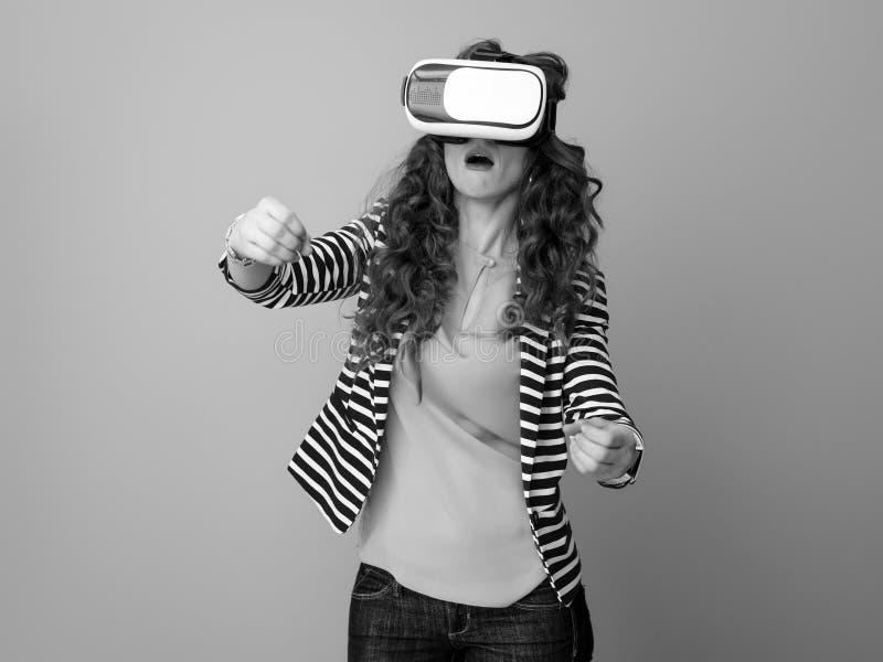 背景的妇女使用VR耳机和驾驶 库存图片