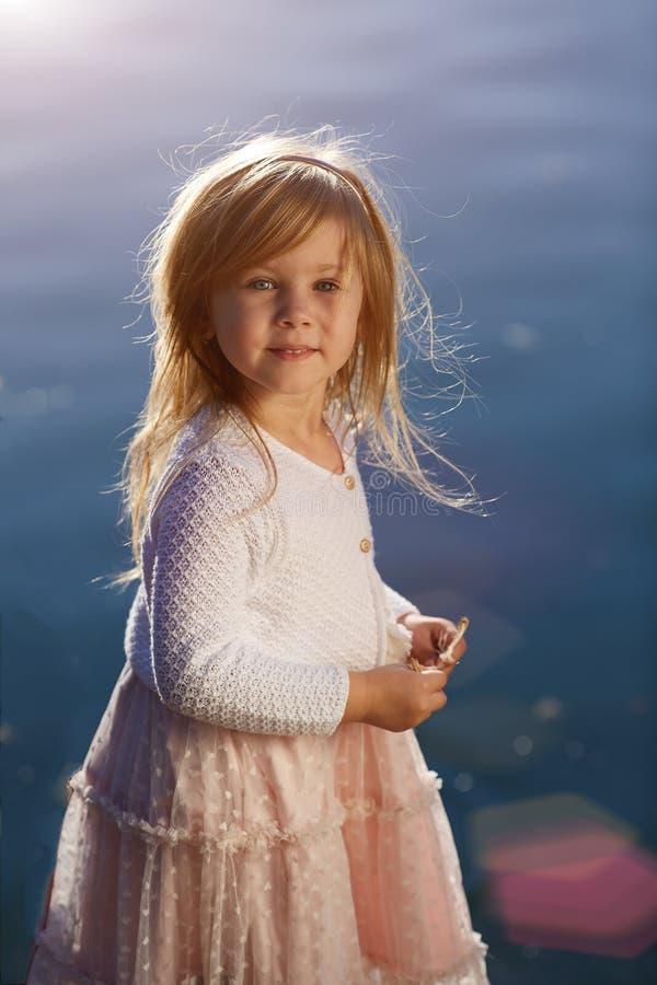 水背景的小女孩,画象每晴天 免版税库存照片