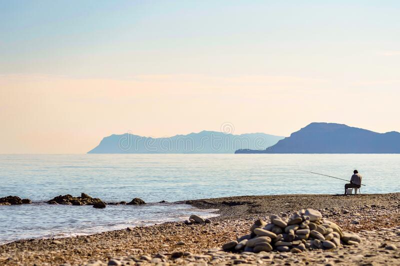 背景的沙滩上钓鱼 免版税库存照片
