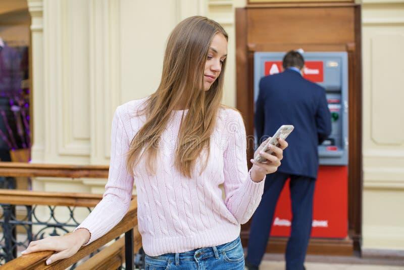 背景的白肤金发的妇女在购物中心ATM 图库摄影