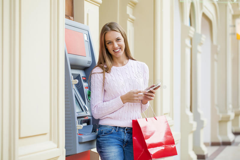 背景的白肤金发的妇女在购物中心ATM 库存图片
