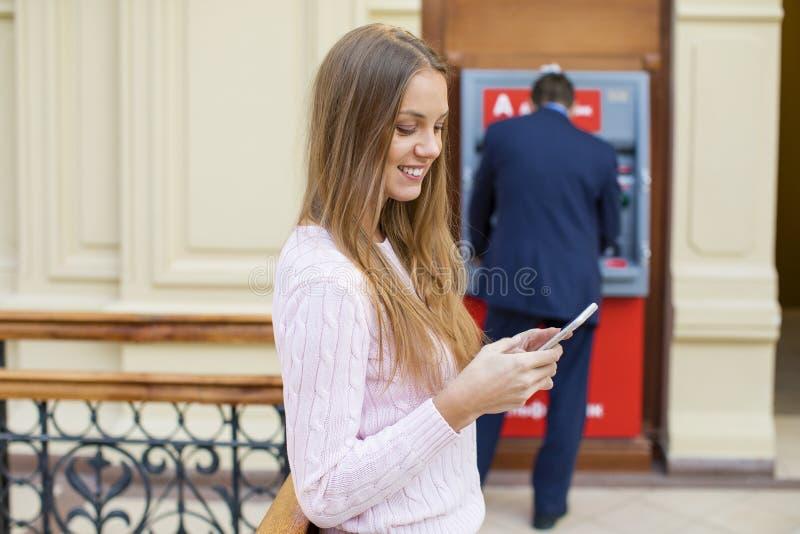 背景的白肤金发的妇女在购物中心ATM 免版税库存照片