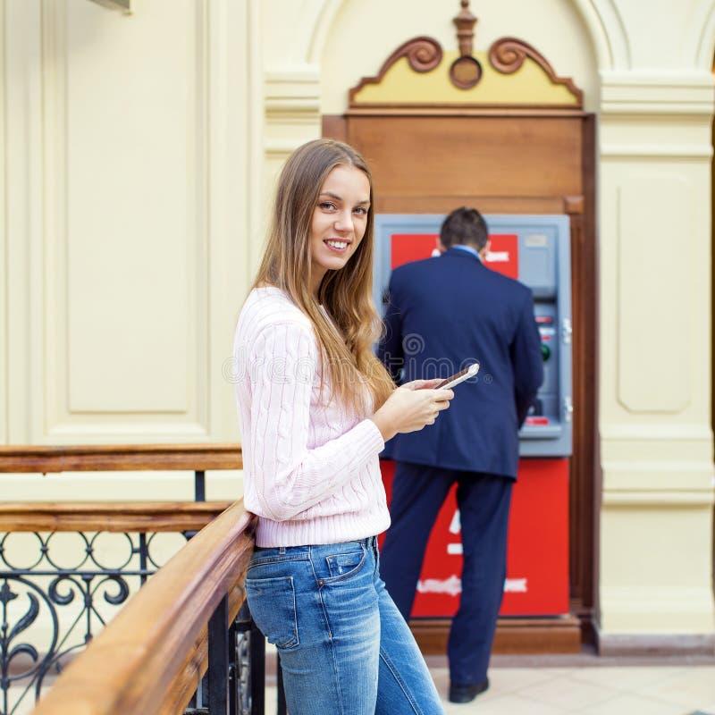 背景的白肤金发的妇女在购物中心ATM 免版税库存图片