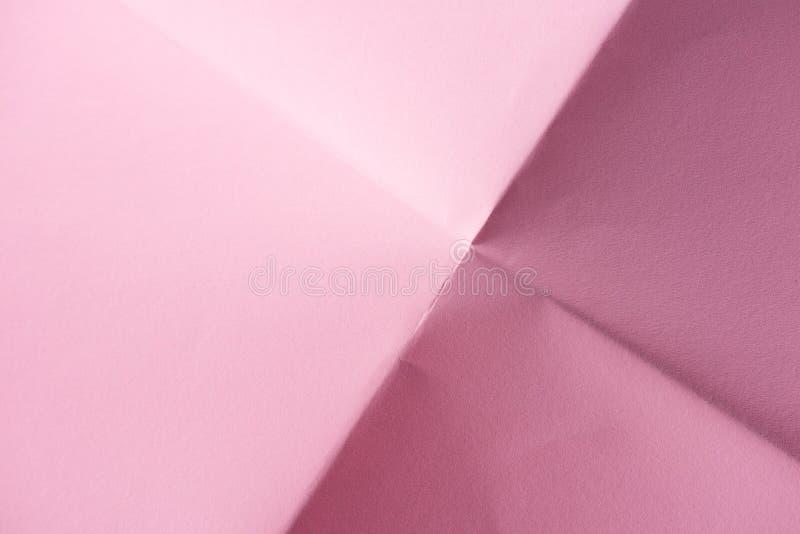 背景的被折叠的桃红色纸 库存图片