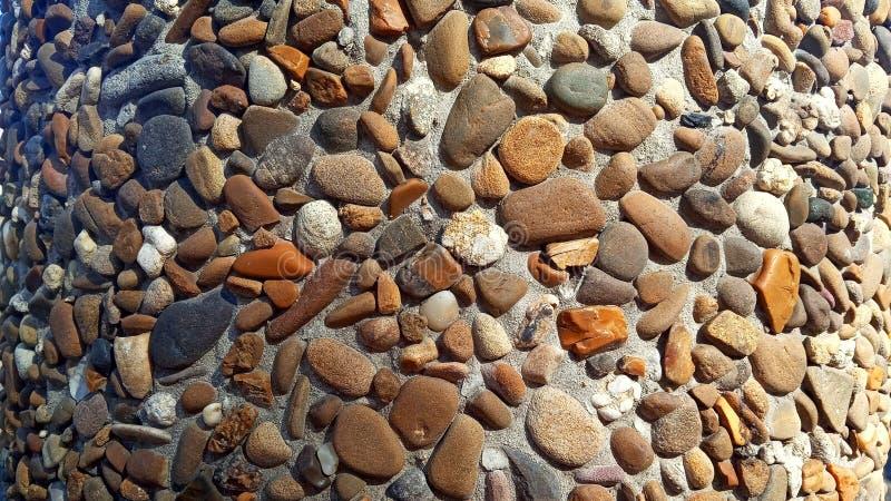 背景纹理在一个混凝土墙的许多橙色和棕色小卵石 库存照片