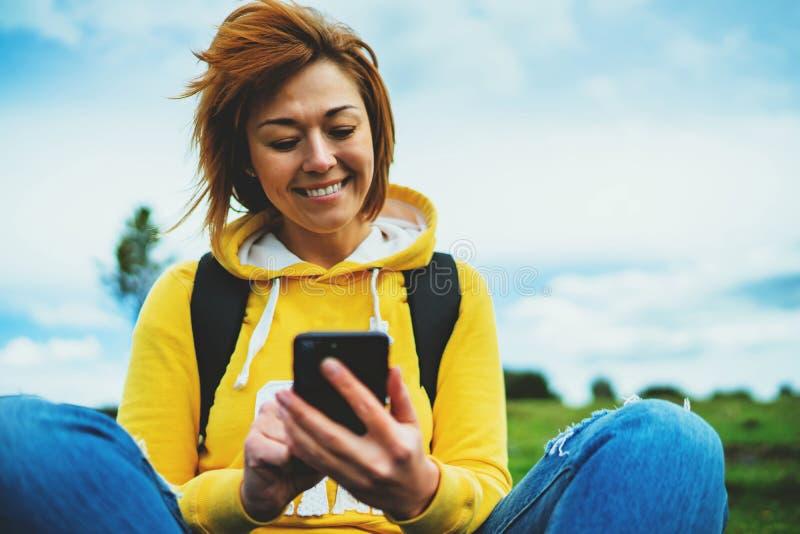 背景绿草的旅游年轻微笑女孩使用流动智能手机,妇女举行在女性手小配件技术的,徒步旅行者 图库摄影
