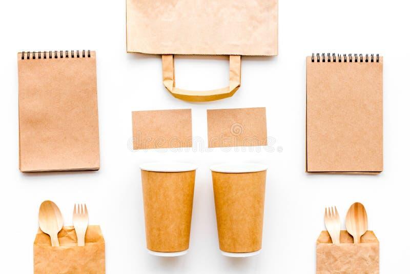 背景色的一次性叉子玻璃塑料集合碗筷透明白色 纸杯,匙子,在包装纸袋子和笔记本样式白色背景的顶视图嘲笑附近分叉 图库摄影