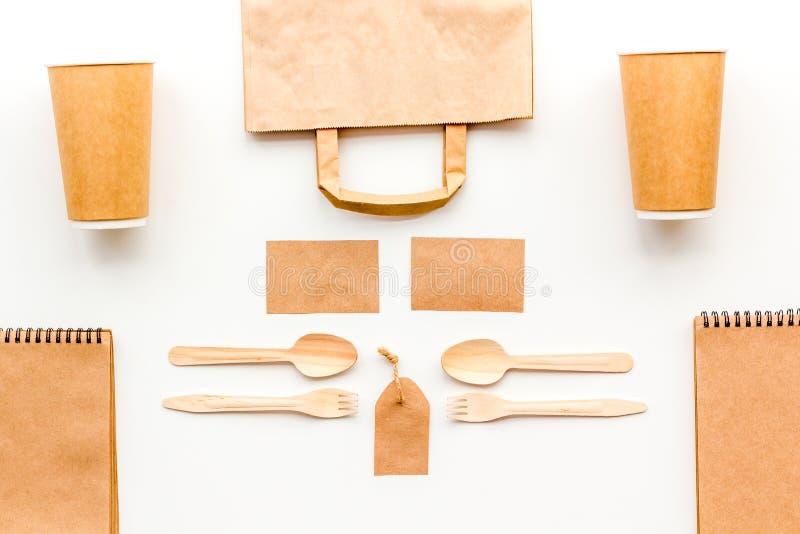 背景色的一次性叉子玻璃塑料集合碗筷透明白色 纸杯,匙子,在包装纸样式白色的袋子、标签和笔记本顶视图嘲笑附近分叉 库存图片