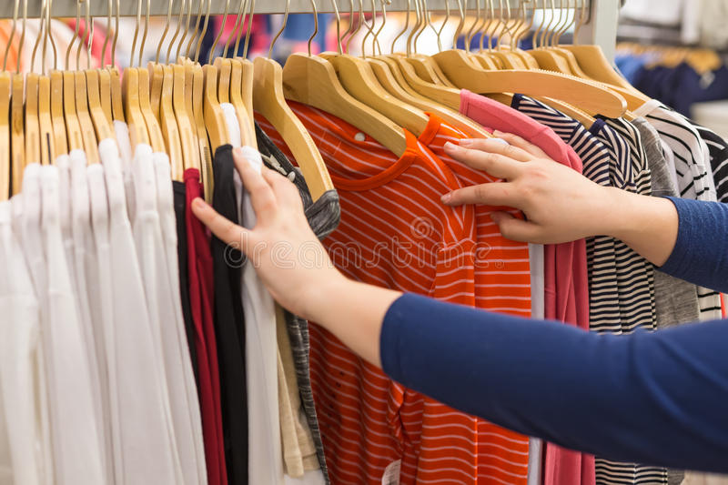背景袋子概念行程购物的白人妇女 妇女选择在挂衣架的衬衣在服装店 选择聚焦 免版税库存图片