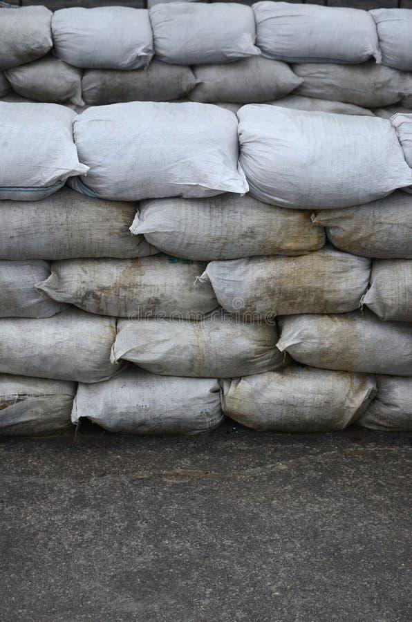背景许多肮脏的沙子为洪水防御请求 防护沙袋护拦为军事使用 英俊的作战地堡 免版税图库摄影