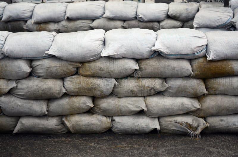 背景许多肮脏的沙子为洪水防御请求 防护沙袋护拦为军事使用 英俊的作战地堡 图库摄影