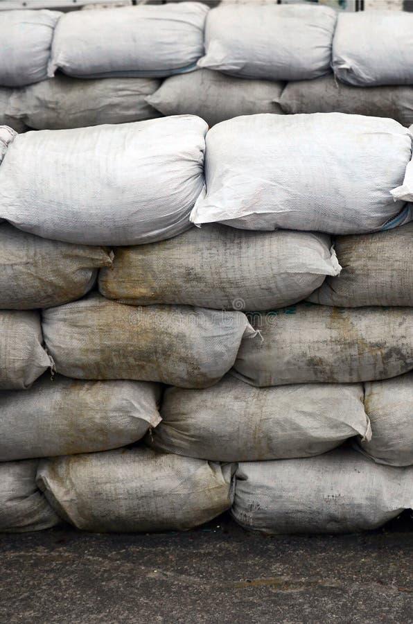 背景许多肮脏的沙子为洪水防御请求 防护沙袋护拦为军事使用 英俊的作战地堡 库存照片